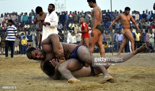 Wrestlers perform all the trades of winning the fight tournament at Sorkha village on December 14 2013 in Noida India Kushti is India's traditional...