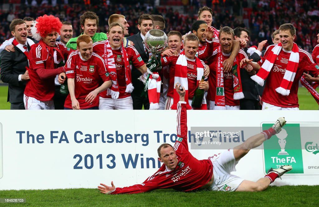 Wrexham players celebrate with the trophy as player manager Andy Morrell slides in to celebrate during the FA Trophy Final match between Wrexham and Grimsby Town at Wembley Stadium on March 24, 2013 in London, England.