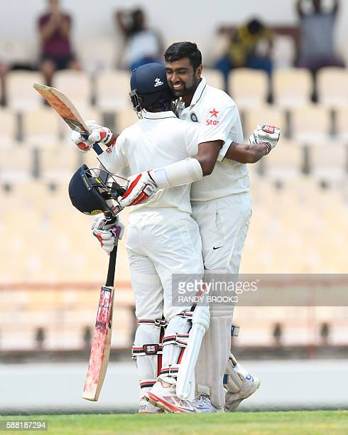 Wriddhiman Saha and Ravichandran Ashwin hug in celebration of both of their centuries during day 2 of the 3rd Test between West Indies and India on...