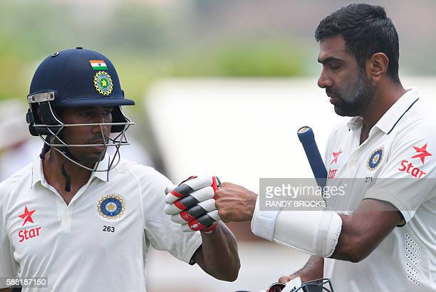 Wriddhiman Saha and Ravichandran Ashwin of India leave the field at lunch during day 2 of the 3rd Test between West Indies and India on August 10...