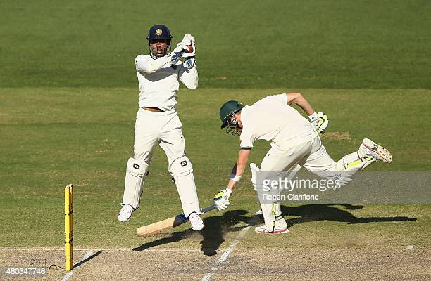Wriddhiman Saha of India takes the ball as Steve Smith of Australia makes his ground during day four of the First Test match between Australia and...