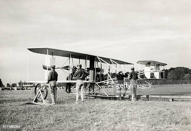 Wright Brothers' Flyer in the starting position on the track Orville Wright is testing the struts prior to starting the first endurance flight The...