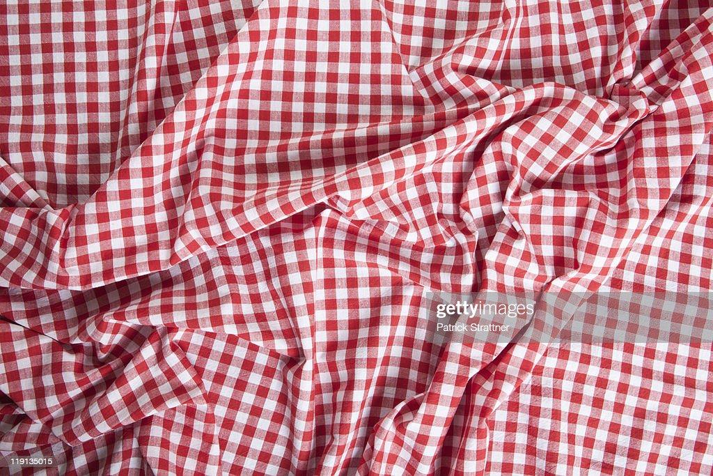A wrinkled gingham picnic blanket