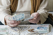 Closeup wrinkled hands of a senior woman counting Turkish Lira banknotes