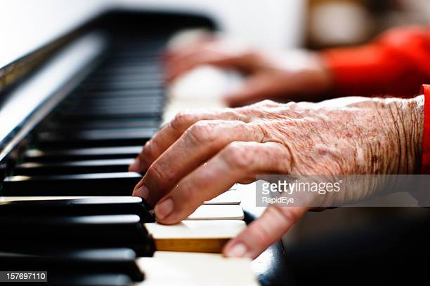 Wrinkled hands of an old person play the piano
