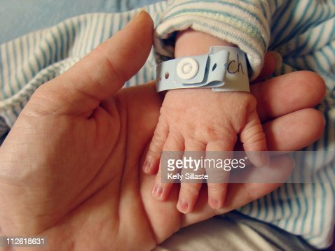 Wrinkled newborn hand with hospital bracelet : Stock Photo
