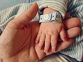 Wrinkled newborn hand with hospital bracelet