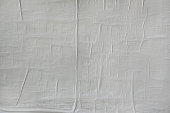 Texture of blank paper poster glued on the wall. Wrinkled, creased.