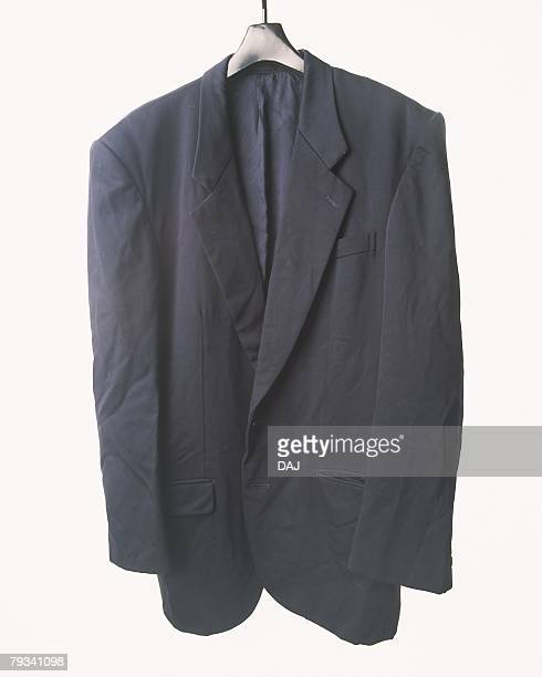 Wrinkled suit jacket hung at white wall