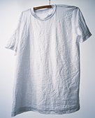 Wrinkled T-shirt hung at white wall
