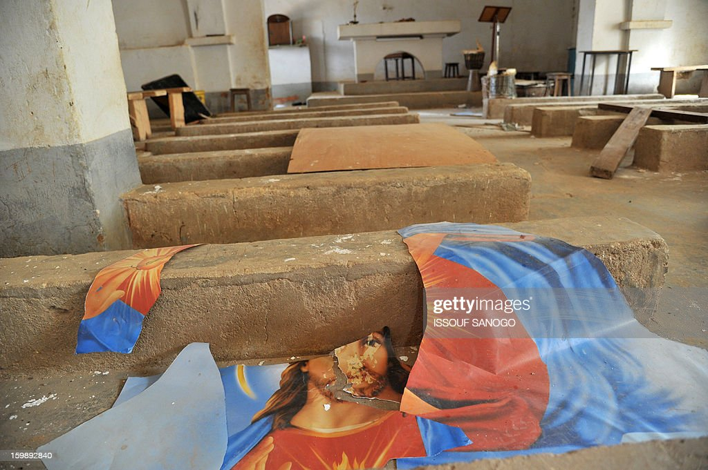 A wripped up image of Jesus Christ is left on the ground of a Catholic church in Diabaly, on January 22, 2013. The EU executive today announced 20 million euros of extra humanitarian aid to help tens of thousands of Malians fleeing fighting in the nation's north and centre, its second such donation in as many months. AFP PHOTO / ISSOUF SANOGO