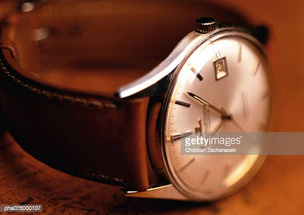 Wristwatch with white face and leather band, wood background, close-up