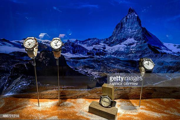 Wristwatches are displayed in a showcase next to a picture of the famous Swiss mountain Matterhorn on March 18 2015 at the booth of the watchmaker...