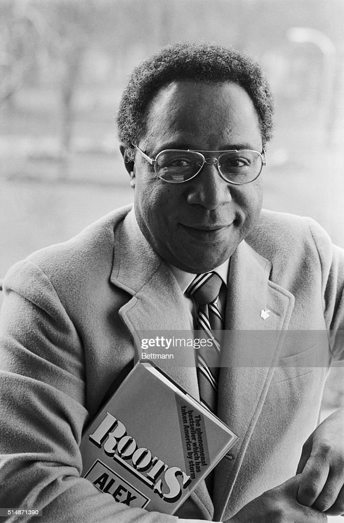 Writer Alex Haley holds a copy of his book Roots during a visit to London.