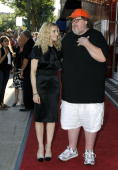 Writer and executive producer Madonna stands with filmmaker Michael Moore at The State Theater for a screening of the new film 'I Am Because We Are'...