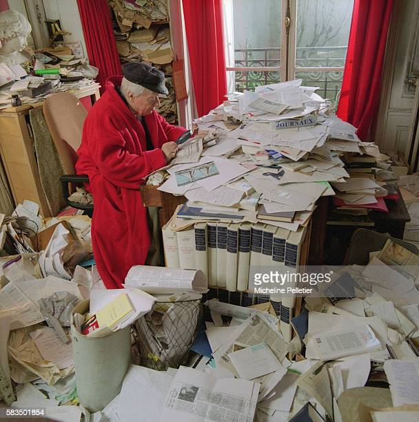 Writer and journalist Paul Guth sits in his home among piles of papers