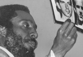 Writer and social activist Dick Gregory holding a picture of Lee Harvey Oswald at Morgan State University Baltimore Maryland September 25 1975