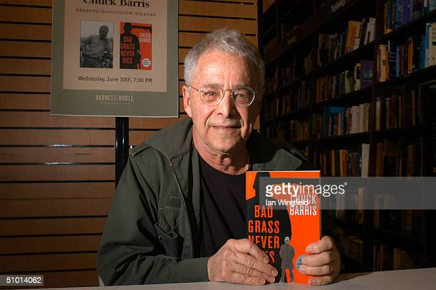 Writer Chuck Barris holds up his newest book 'Bad Grass Never Dies' during a book signing June 30 2004 in New York City