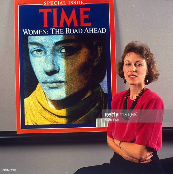 TIME writer Claudia Wallis standing in front of enlarged cover of TIME magazine w the headline WOMEN THE ROAD AHEAD