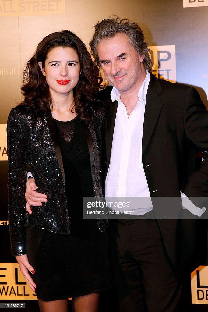 Writer Jean-Christophe Grange (R) and companion Carmen Fernandez Santa Cruz attend the photocall before the party for 'The Wolf of Wall Street' World Premiere. Held at Palais Brogniart on December 9, 2013 in Paris, France.
