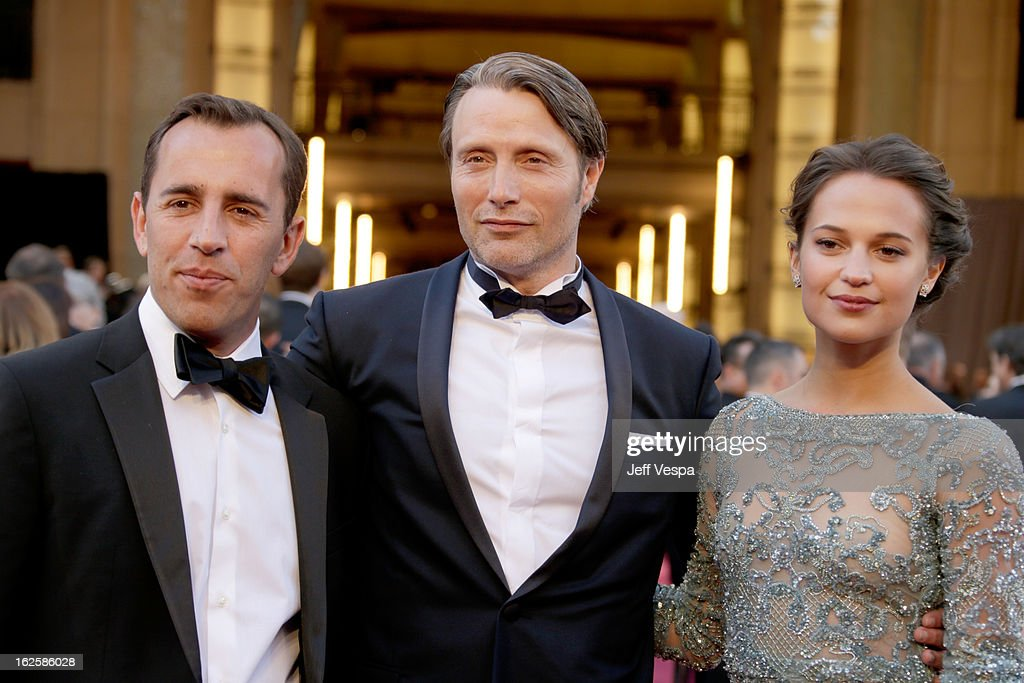 Writer Nikolaj Arcel, actor Mads Mikkelsen and Alicia Vikander arrive at the Oscars at Hollywood & Highland Center on February 24, 2013 in Hollywood, California.