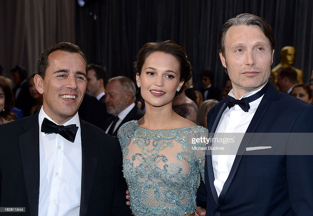 Writer Nikolaj Arcel, actress Alicia Vikander and writer Mads Mikkelsen arrives at the Oscars at Hollywood & Highland Center on February 24, 2013 in Hollywood, California.