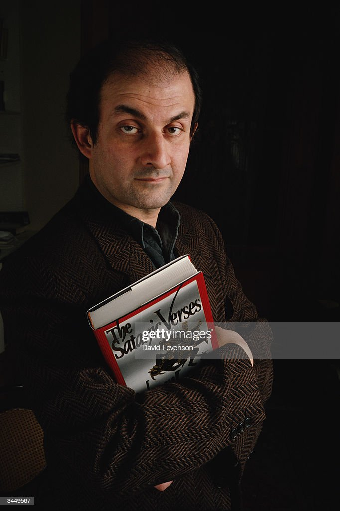 Writer Salman Rushdie poses at his home in Islington, in London, England holding a copy of 'The Satanic Verses' on January 18, 1991. One month later Ayatollah Khomeini placed a 'fatwa' on him, claiming the book was blasphemous against Islam, and Rushdie was forced into hiding.