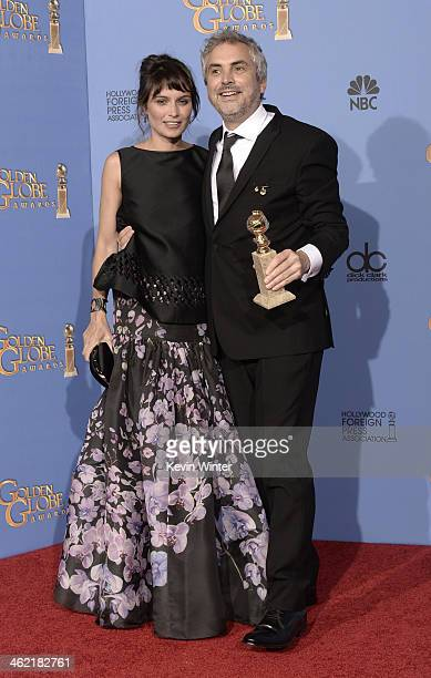 Writer Sheherazade Goldsmith and Director Alfonso Cuaron winner of Best Director for 'Gravity' pose in the press room during the 71st Annual Golden...