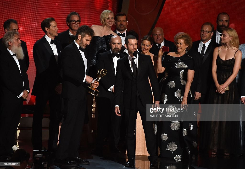 Writer/producers David Benioff (4L), and D.B. Weiss (C) with cast and crew accept the award for Outstanding Drama Series for 'Game of Thrones' during the 68th Emmy Awards show on September 18, 2016 at the Microsoft Theatre in downtown Los Angeles. / AFP / Valerie MACON