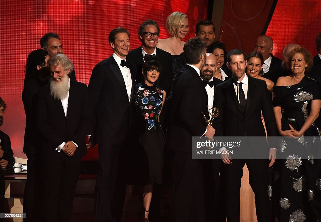 Writer/producers David Benioff (4L), and D.B. Weiss (2R) with cast and crew accept the award for Outstanding Drama Series for 'Game of Thrones' during the 68th Emmy Awards show on September 18, 2016 at the Microsoft Theatre in downtown Los Angeles. / AFP / Valerie MACON
