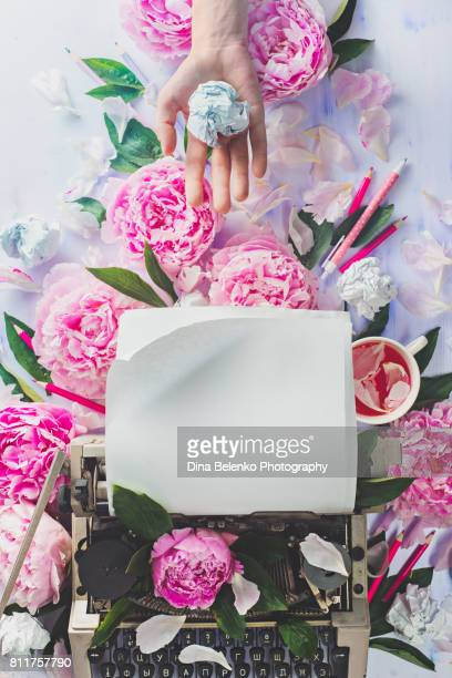 Writer's workplace with typewriter, stationary, crumpled paper and pink peony flowers
