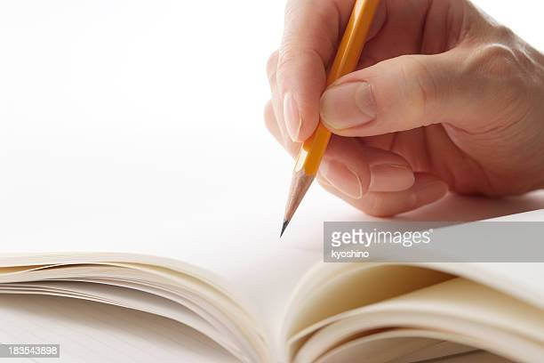Writing a notebook by yellow pencil on white background