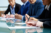 Close-up of business people in board room. They sitting in a row and writing in paper. They sitting at conference table at meeting. They studying at seminar. It is perfect for using it in commercial a