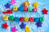 writing hello february on toy wooden colour cubes with decor and light blue background.