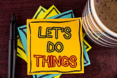Writing note showing  Let Us Do Things. Business photo showcasing Try something new find happiness mastering it by practice written Sticky Note paper Wooden background Coffee Cup and Marker