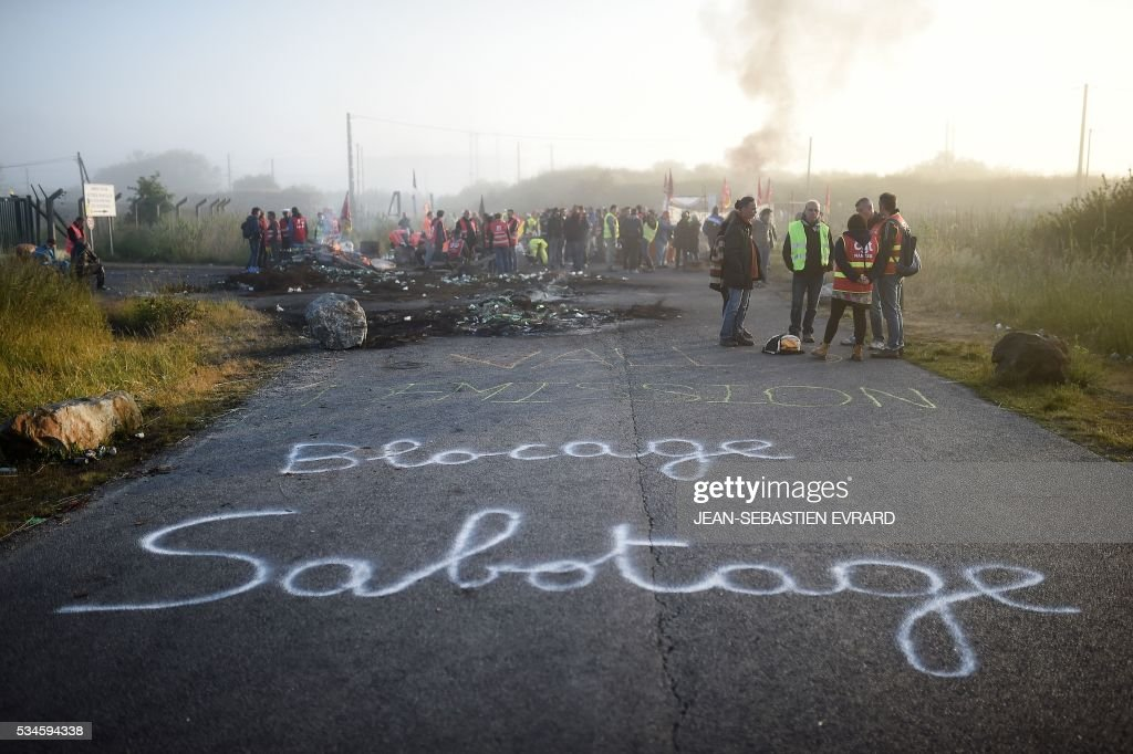 A writing on the road reads 'blockage, sabotage' as workers on strike block the access to an oil depot near the Total refinery of Donges, western France, on May 27, 2016 to protest against the government's planned labour law reforms The French government's labour market proposals, which are designed to make it easier for companies to hire and fire, have sparked a series of nationwide protests and strikes over the past three months. French unions on May 27 called on workers to 'continue and step up their action', as a wave of strikes against a disputed labour law disrupted transport and fuel supplies. / AFP / JEAN