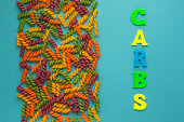 Writing text showing carb of multicolored letters. Colorful background. Abstract set on colorful backdrop with colored spiral pasta. Nutrients dietary concept. headline