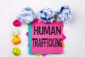 Writing text showing Human Trafficking written on sticky note in office with screw paper balls. Business concept for Slavery Crime Prevention on the isolated background.