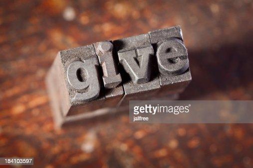 GIVE written in letterpress on old wood background