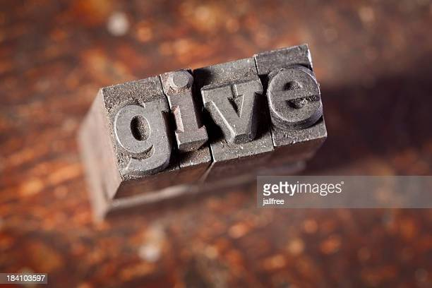 GIVE written in letterpress on old wood background