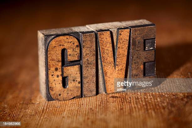 GIVE written in wooden letterpress on wood background