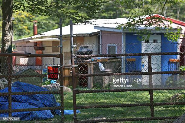 A written 'Lot 11' on a Beware of Dog sign on a fenced gate with barbed wire on the farm of one of the renters at Medeiros Farm in Westport Mass on...