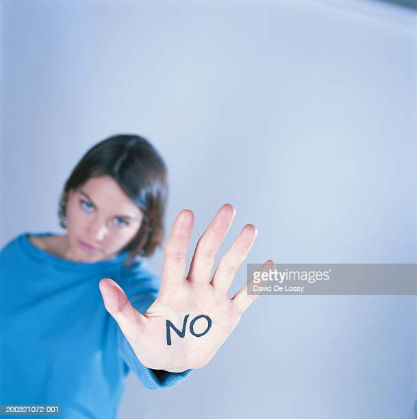 'NO' written on palm of young woman (focus on palm)
