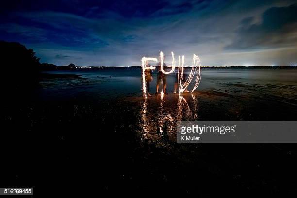 'FUN' written with sparklers on dark beach
