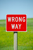 A bright red and white sign tells travelers that they are headed the wrong way.  Set against a field of yellow clover and a blue sky, this message could be used in a variety of ways and there is plent