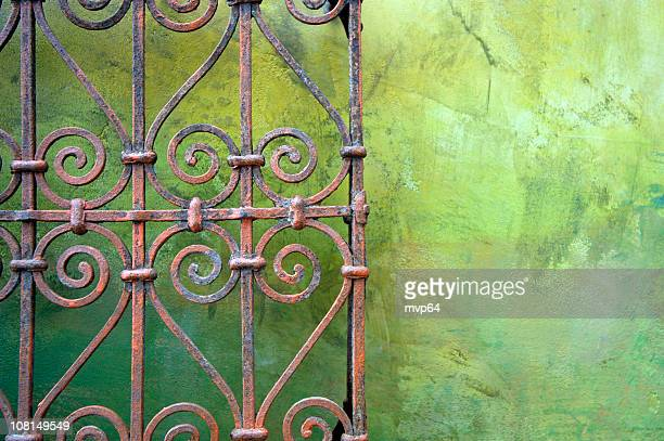 Wrought iron fence against green wall