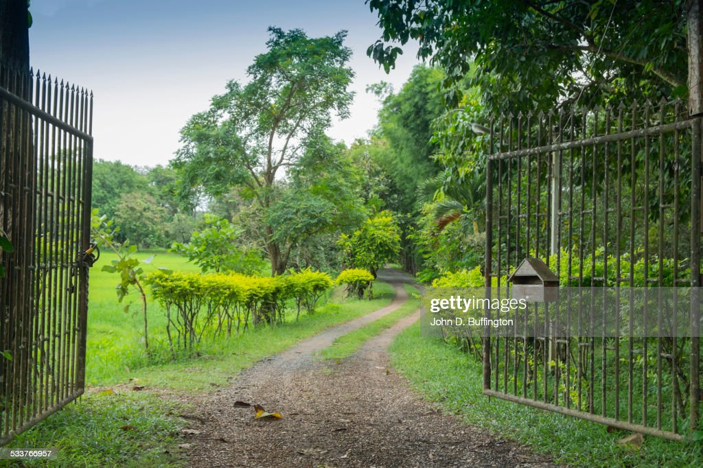 Wrought iron gates opening onto dirt road