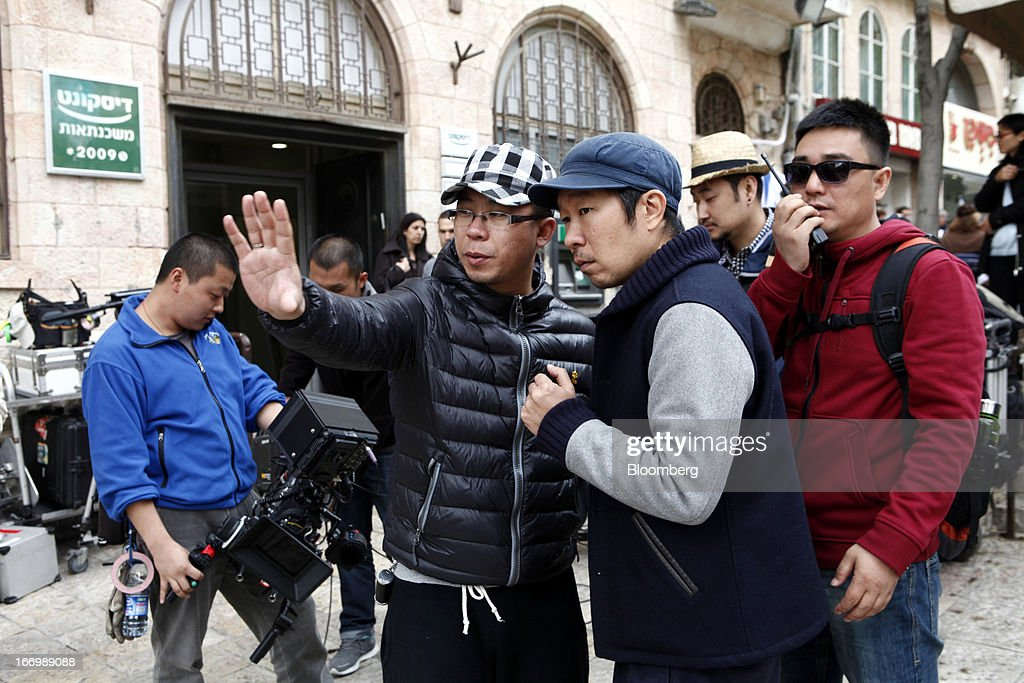 Wu Bai, Chinese film director, left, directs cameraman Charlie Lam from Chuan Films whilst filming on the set of 'The Old Cinderella' at the Ben Yehuda pedestrian mall in Jerusalem, Israel, on Friday, April 19, 2013. The Bank of Israel governor said Europe remains the weak link in the world economy and European Union officials need to tackle the continent's banking difficulties. Photographer: Ariel Jerozolimski/Bloomberg via Getty Images