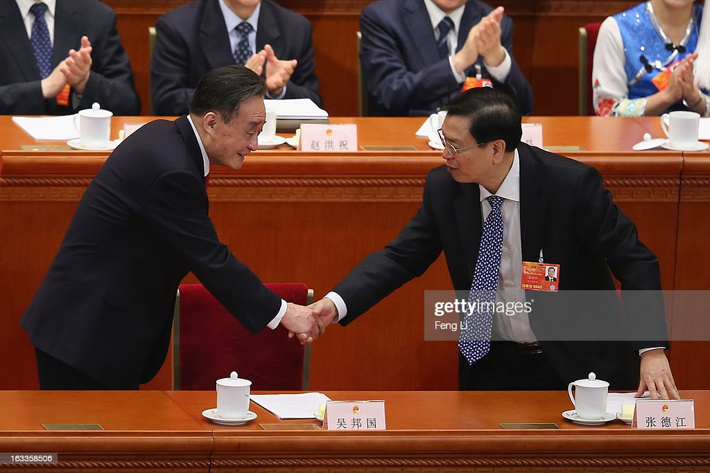 Wu Bangguo outgoing Chairman of the National People's Congress shakes hands with his replacement Zhang Dejiang during a plenary session of the NPC...