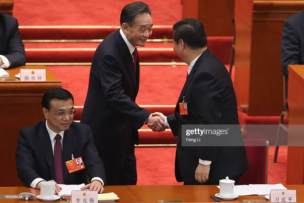 Wu Bangguo outgoing Chairman of the National People's Congress shakes hands with Chinese Communist Party General Secretary Xi Jinping near Chinese...